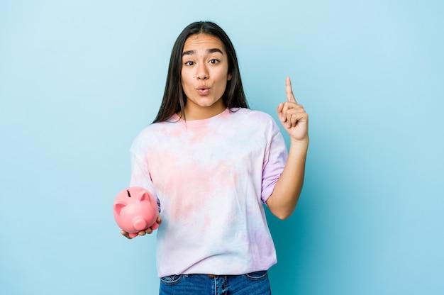 Junge asiatische frau, die eine rosa bank über isolierter wand hält, die eine große idee, konzept der kreativität hat.