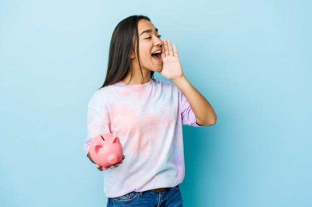 Junge asiatische frau, die eine rosa bank über isolierter wand hält, die handfläche nahe geöffnetem mund schreit und hält.