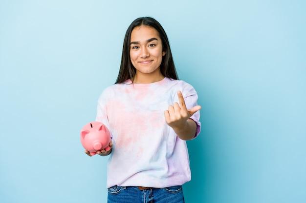 Junge asiatische frau, die eine rosa bank über isolierter wand hält, die mit dem finger auf sie zeigt, als ob die einladung näher kommt