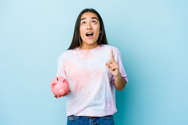 Junge asiatische frau, die eine rosa bank über isolierter wand hält, die oben mit geöffnetem mund zeigt.