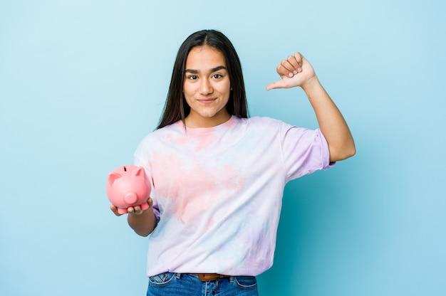Junge asiatische frau, die eine rosa bank über isolierter wand hält, fühlt sich stolz und selbstbewusst, beispiel zu folgen.