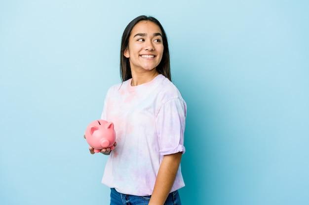 Junge asiatische frau, die eine rosa bank über isolierter wand hält, schaut lächelnd, fröhlich und angenehm beiseite.