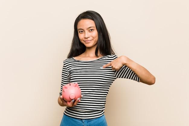 Junge asiatische frau, die eine sparschweinperson eigenhändig zeigt auf einen hemdkopienraum, stolz und überzeugt hält