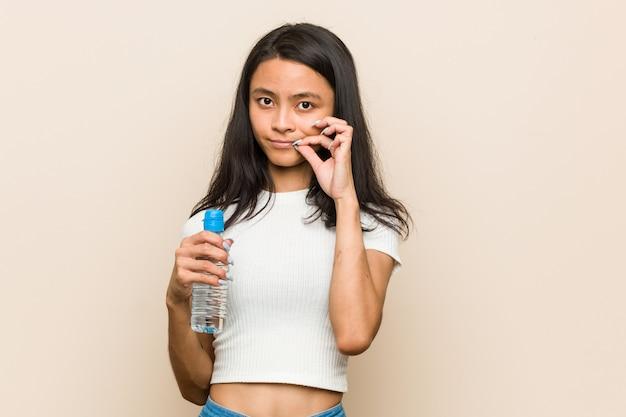 Junge asiatische frau, die eine wasserflasche mit den fingern auf den lippen halten ein geheimnis hält.