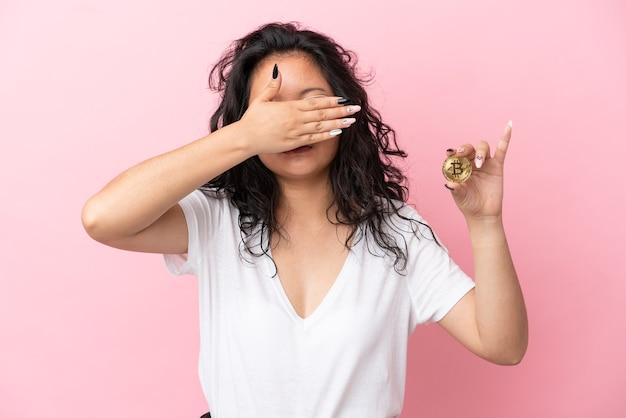 Junge asiatische frau, die einen bitcoin auf rosafarbenem hintergrund isoliert hält und die augen mit den händen bedeckt. will etwas nicht sehen