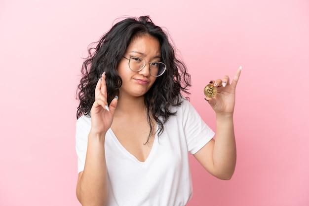 Junge asiatische frau, die einen bitcoin auf rosafarbenem hintergrund mit gekreuzten fingern hält und das beste wünscht