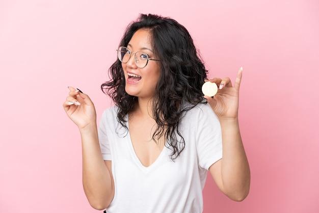 Junge asiatische frau, die einen bitcoin einzeln auf rosafarbenem hintergrund hält und beabsichtigt, die lösung zu realisieren, während sie einen finger nach oben hebt