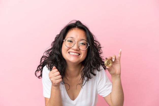 Junge asiatische frau, die einen bitcoin einzeln auf rosafarbenem hintergrund hält und einen sieg in der gewinnerposition feiert