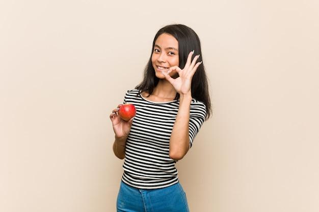Junge asiatische frau, die einen fröhlichen und selbstbewussten apfel hält, der ok geste zeigt.