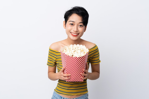 Junge asiatische frau, die einen großen eimer popcorn hält