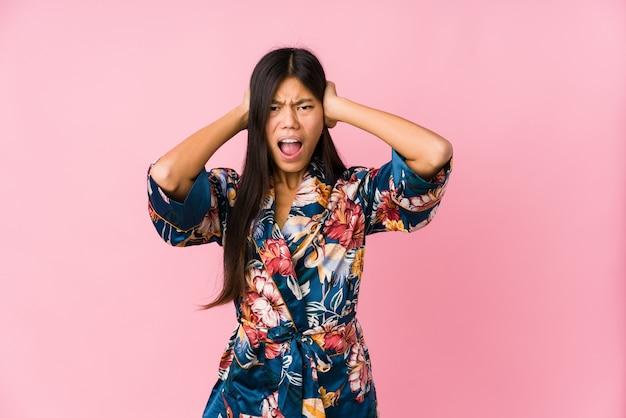 Junge asiatische frau, die einen kimono-pyjama trägt, der ohren mit händen bedeckt, die versuchen, nicht zu lautes geräusch zu hören.