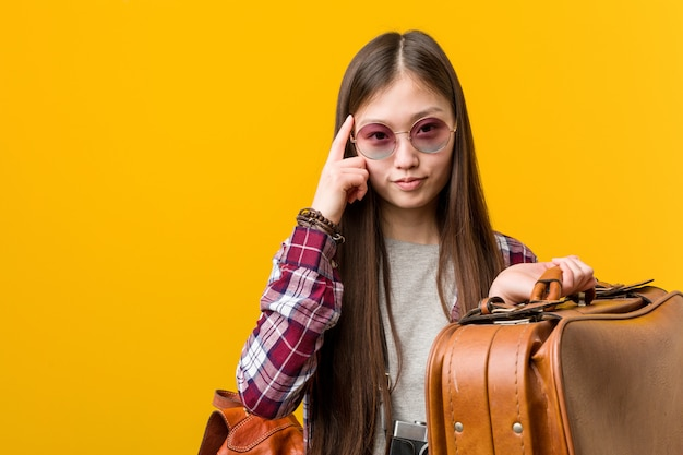 Junge asiatische frau, die einen koffer hält, der seine schläfe mit dem finger zeigt und denkt, konzentrierte sich auf eine aufgabe.