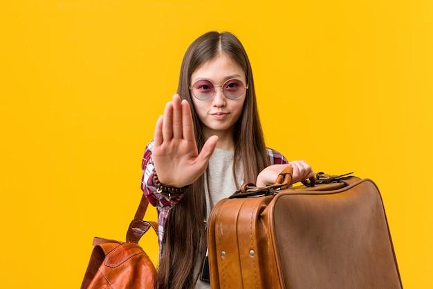 Junge asiatische frau, die einen koffer steht mit der ausgestreckten hand zeigt das stoppschild und verhindert sie hält.