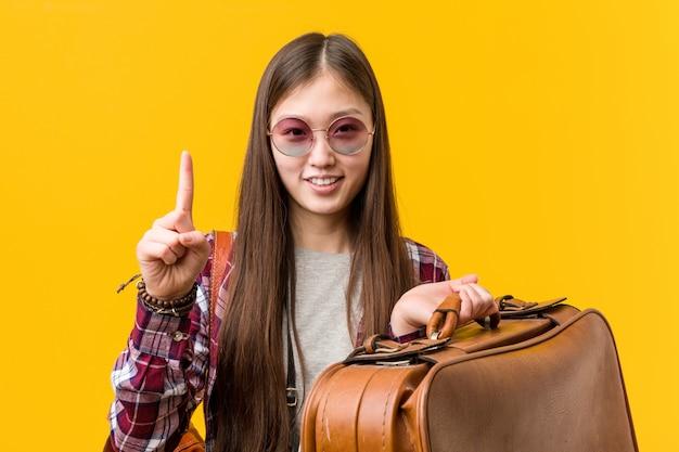 Junge asiatische frau, die einen koffer zeigt nummer eins mit dem finger hält.