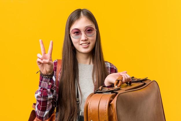 Junge asiatische frau, die einen koffer zeigt nummer zwei mit den fingern hält.