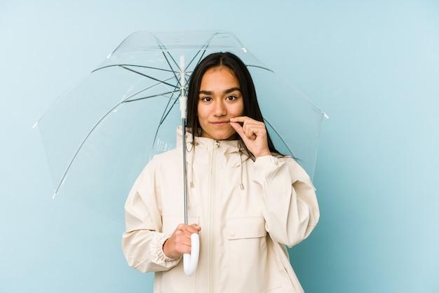 Junge asiatische frau, die einen regenschirm mit den fingern auf den lippen hält, die ein geheimnis halten.