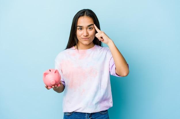 Junge asiatische frau, die einen rosa bankzeigetempel mit dem finger hält, denkend, konzentrierte sich auf eine aufgabe.