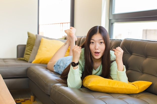 Junge asiatische frau, die einen unglaublichen erfolg wie ein gewinner feiert, aufgeregt und glücklich sagt, nimm das!