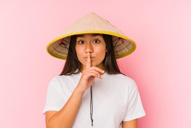 Junge asiatische frau, die einen vietnamesischen hut trägt isoliert junge asiatische frau, die einen vietnaminischen hut trägt, der ein geheimnis hütet oder um stille bittet