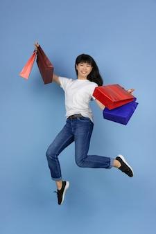 Junge asiatische frau, die einkaufstaschen hält und auf blau springt
