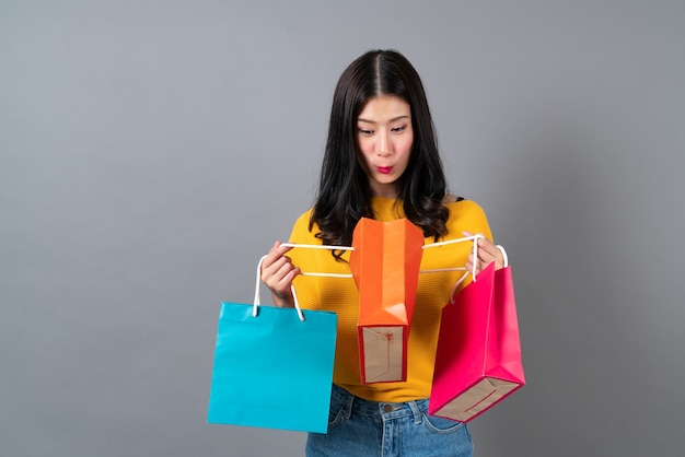 Junge asiatische frau, die einkaufstaschen hält