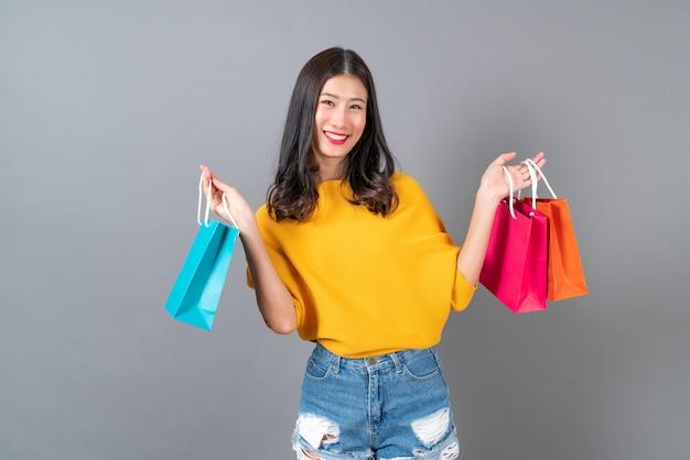 Junge asiatische frau, die einkaufstaschen im gelben hemd auf grauer wand hält