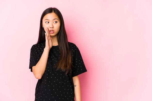 Junge asiatische frau, die elegante kleidung isoliert trägt, sagt eine geheime heiße bremsnachricht und schaut zur seite