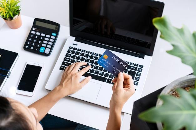 Junge asiatische frau, die forschungsarbeit für ihr geschäft mit computer-laptop tut, während kreditkarte zu hause, draufsicht und kopienraum hält