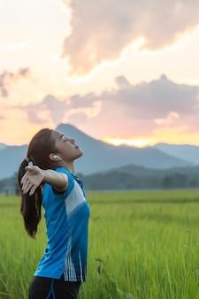 Junge asiatische frau, die frühlingsbrise auf dem reisgebiet mit sonnenuntergang genießt