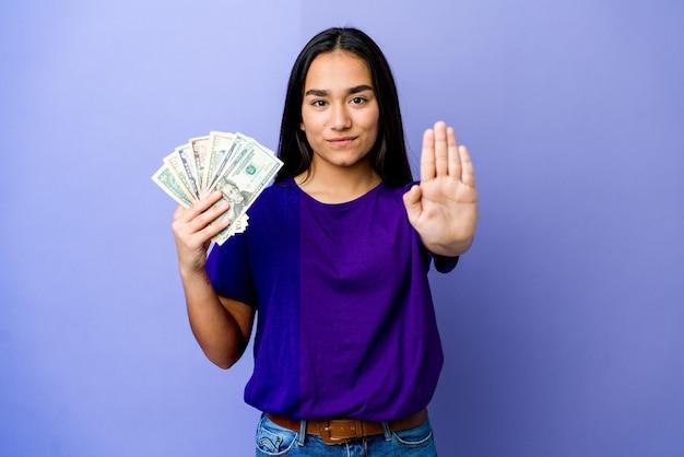 Junge asiatische frau, die geld hält, das mit ausgestreckter hand steht und stoppschild zeigt, das sie verhindert.