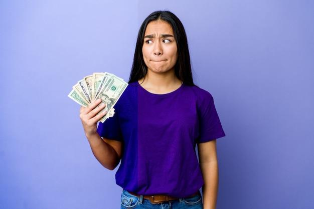 Junge asiatische frau, die geld isoliert auf lila verwirrt hält, fühlt sich zweifelhaft und unsicher.