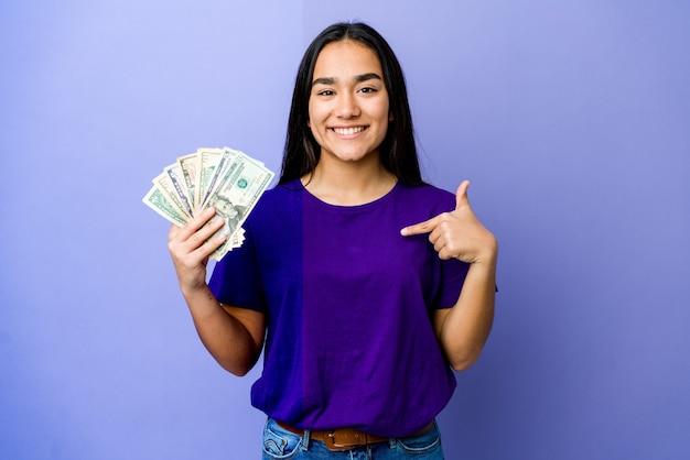 Junge asiatische frau, die geld lokalisiert auf lila wandperson hält, die von hand auf einen hemdkopierraum zeigt, stolz und zuversichtlich