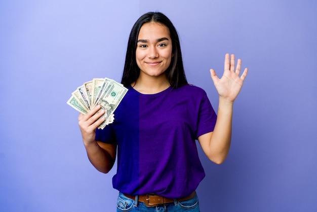 Junge asiatische frau, die geld lokalisiert auf purpurroter wand hält, die fröhlich zeigt nummer fünf mit den fingern.