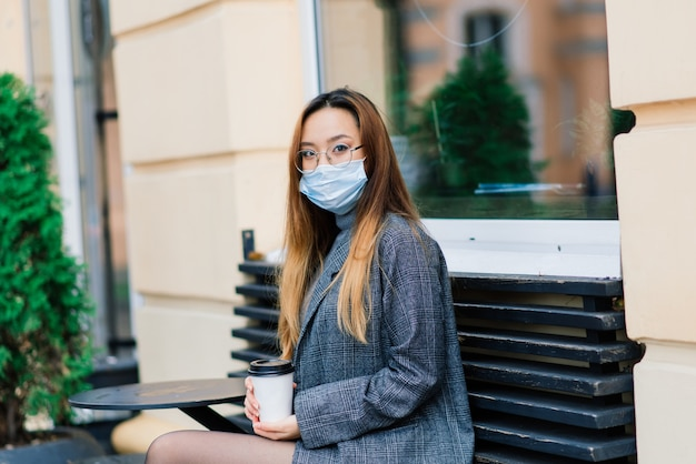 Junge asiatische frau, die gesichtsmaske trägt, die an einer inländischen straße steht