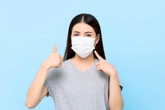 Junge asiatische frau, die gesichtsmaske trägt, die coronavirus und allergien schützt, die daumen lokalisiert auf hellblauer wand geben