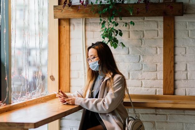 Junge asiatische frau, die gesichtsmaske trägt, steht an einer inländischen straße. neue normale covid-19-epidemie