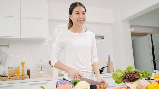 Junge asiatische frau, die gesundes essen des salats in der küche macht