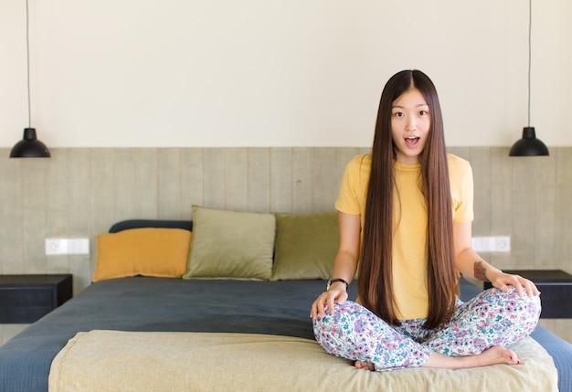 Junge asiatische frau, die glücklich, aufgeregt, überrascht oder schockiert, lächelnd und erstaunt über etwas unglaubliches fühlt