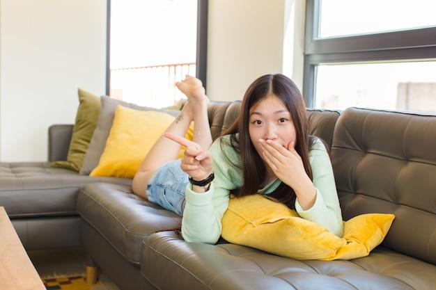Junge asiatische frau, die glücklich, schockiert und überrascht fühlt, mund mit hand bedeckt und auf seitlichen kopierraum zeigt