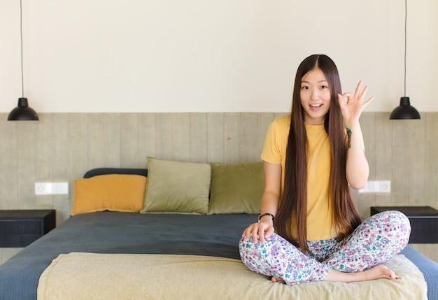 Junge asiatische frau, die glücklich, überrascht, stolz und aufgeregt aussieht und auf sich selbst zeigt