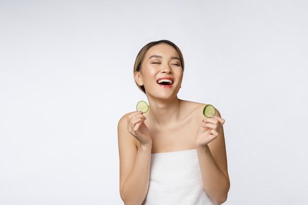 Junge asiatische frau, die gurkenscheibe in ihren händen hält und isst