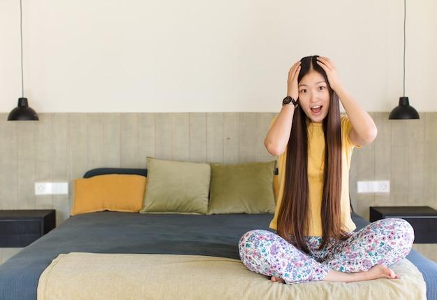 Junge asiatische frau, die hände zum kopf hebt, mit offenem mund, sich extrem glücklich, überrascht, aufgeregt und glücklich fühlt