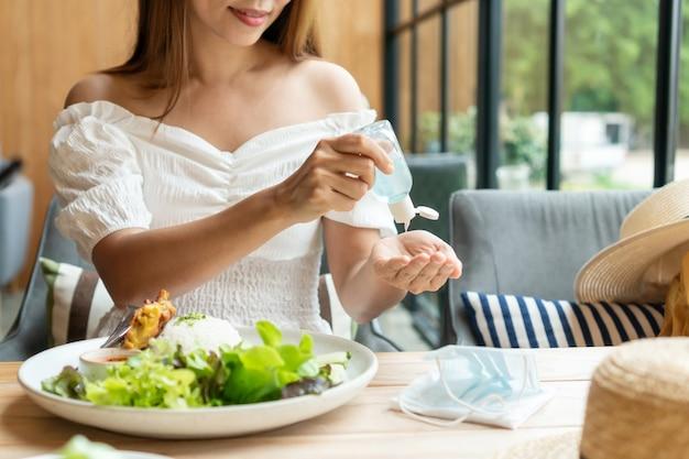 Junge asiatische frau, die händedesinfektionsmittel auf ihre hand anwendet, bevor sie im restaurant isst