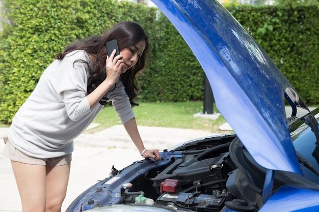 Junge asiatische frau, die handy verwendet, ruft einen automechaniker an, während sie kaputtes auto auf straße betrachtet