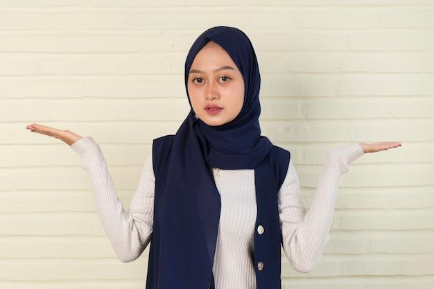 Junge asiatische frau, die hijab lächelnd selbstbewusstes zeigen mit den fingern in verschiedene richtungen trägt.