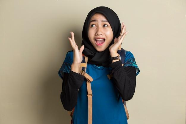 Junge asiatische frau, die hijab-reisenden trägt, schockierte überraschung