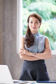 Junge asiatische frau, die hinter schreibtisch im büro mit den gekreuzten armen steht