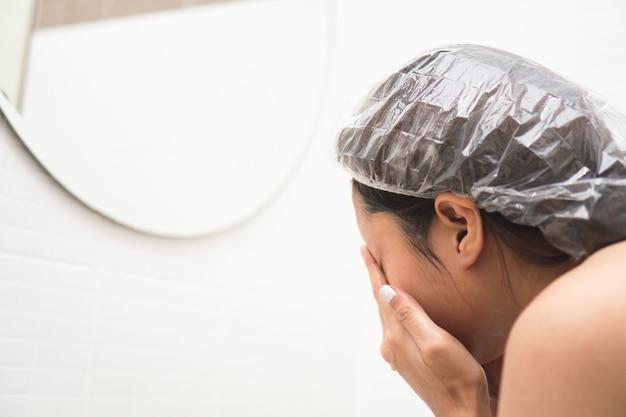Junge asiatische frau, die ihr gesicht vor dusche im badezimmer wäscht.