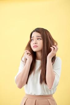 Junge asiatische frau, die ihr haar bürstet und ihr haar enttäuschend konditioniert
