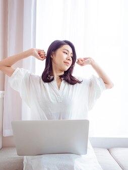 Junge asiatische frau, die ihre arme ausdehnt, nachdem sie laptop verwendet hat.